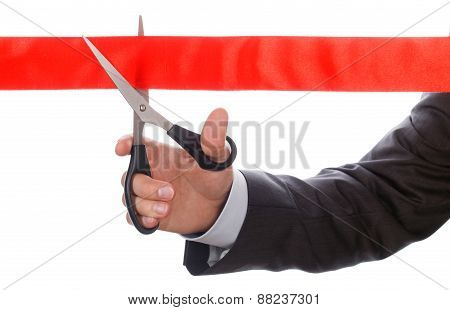 Hand Of Businessman In Suit Cutting Red Ribbon With Pair Of Scissors Isolated On White Background