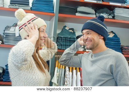 Playful couple trying on hats