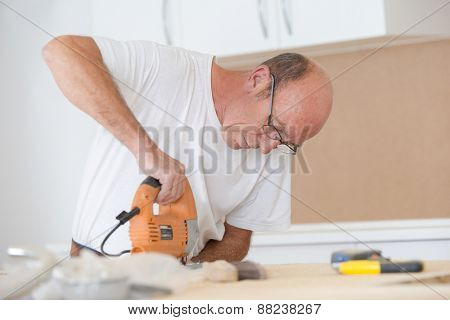 Carpenter using an electric saw to cut wood