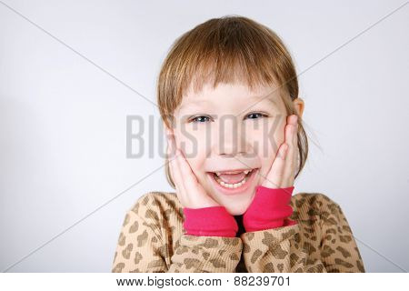 Cute little girl holding hands to face in surprise isolated on white background