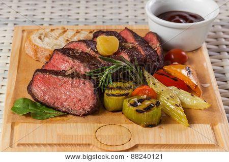 Grilled beef steak on wooden board