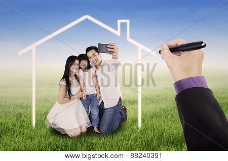 Family Taking Photo Under A Dream House
