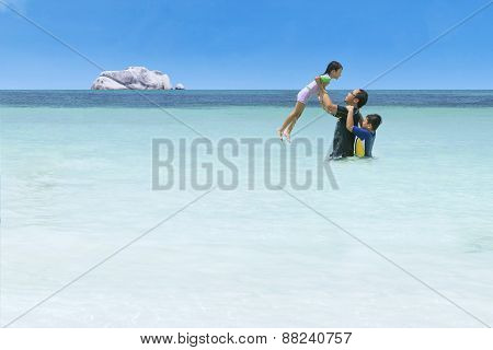 Playful Girl With Her Family On Beach