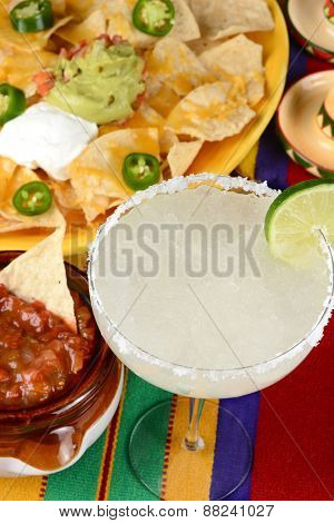 High angle view of a margarita cocktail surrounded by nachos, chips, salsa on a bright Mexican, table cloth. Vertical format. Perfect for Cinco de Mayo projects.