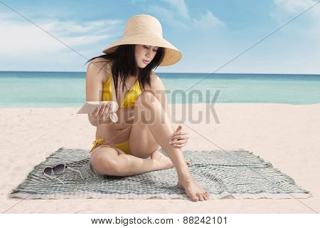 Sexy Lady Using Sunscreen At Beach