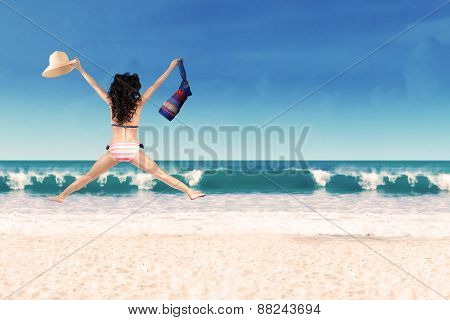 Woman Leaping With Bag And Hat