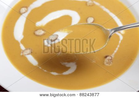 Closeup on a spoonful of traditional French butternut squash soup, garnished with cream and toasted squash seeds