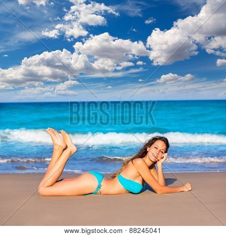 Brunette tourist lying in beach sand tanning happy in summer vacation