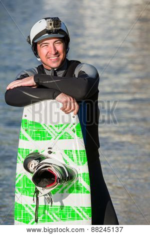 Male wakeboarder posing with his board