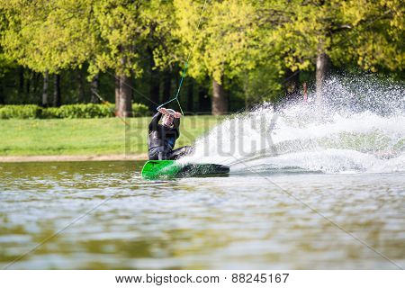 Male wakeboarder in a spray on pond in park
