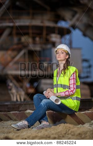 female worker sitting on the sleepers on backgroud of career stacker