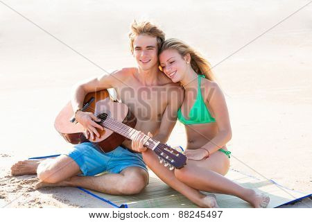 Blond young tourist couple playing guitar at beach