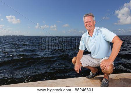 Senior man squatting by the bay