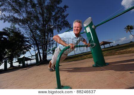 Senior man doing pushups in the park