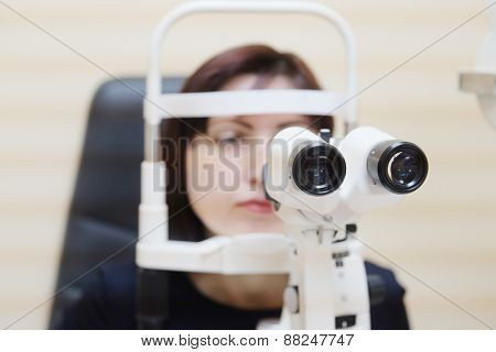Woman looking into eye test machine