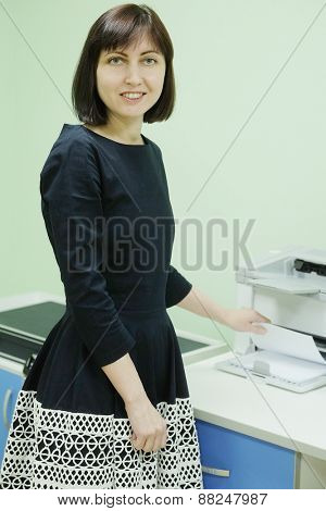 Secretary in office working on printer