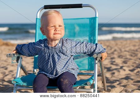 Happy Little Girl Sitting On Chair At Beach