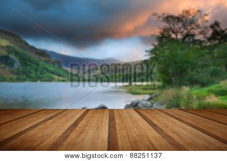 Beautiful Sunrise Over Lake And Mountains With Wooden Planks Floor