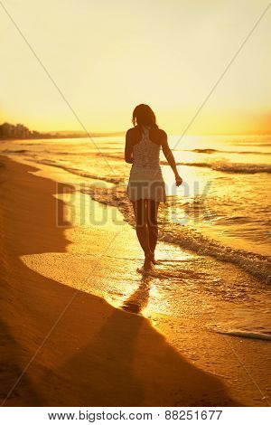 Beautiful Girl Walking Along Beach At Sunset