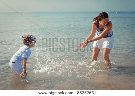 Mom And Son Splashing Water At Sea
