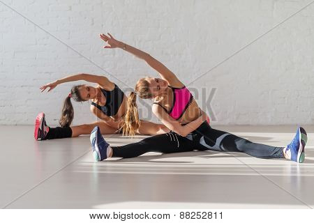 Two beautiful fitness slim  girls doing yoga stretching exercise tilts to side together sitting on t