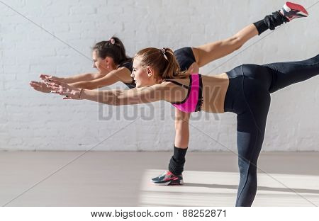 Two pretty fitness girls in the gym doing hard yoga training following sun from window
