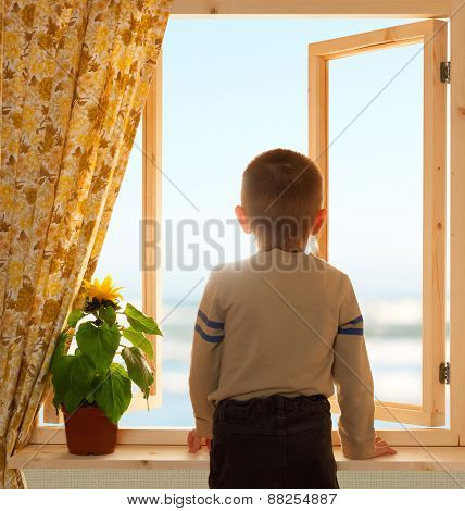 child looking through open window, wooden frame, sea and sky view