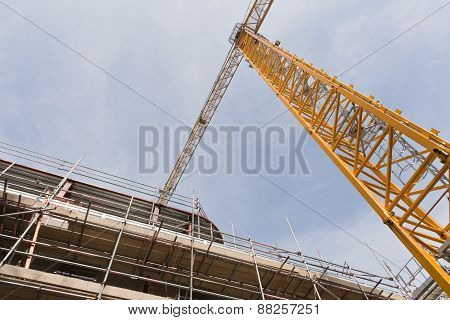 A view looking up to yellow tower crane on a construction site