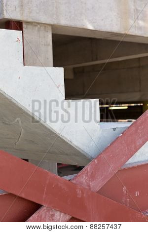 Detail of a concrete stair and red steel stair support on a construction site