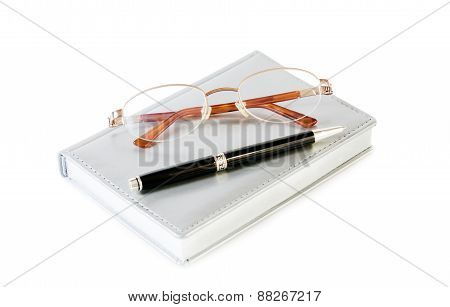 Daily Planner With Glasses And Pen On White Background. Selective Focus On Glasses