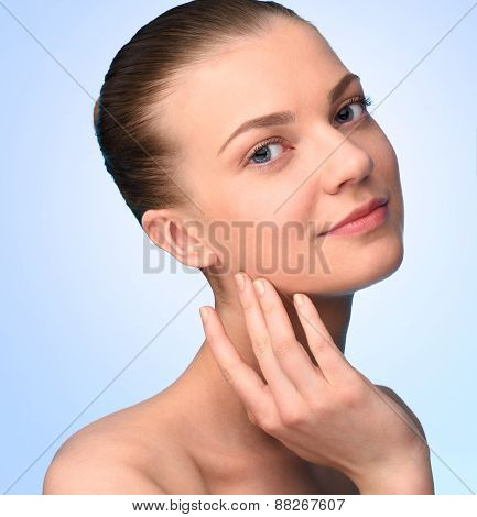Beautiful woman face looking at camera over blue background.