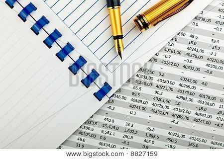 gold metal ink pen, notebook and classic financial document