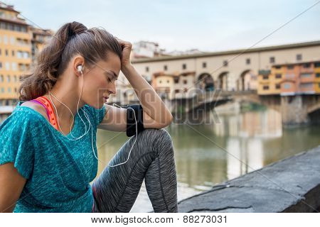 Fitness Woman Sitting Near Ponte Vecchio In Florence, Italy