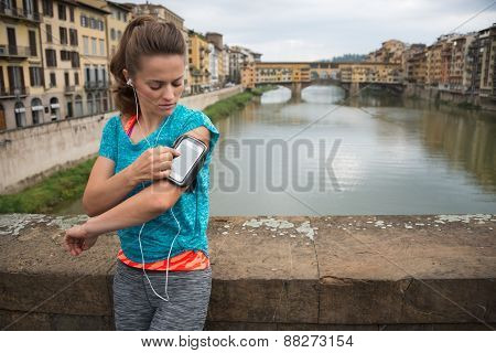 Fitness Woman Using Cell Phone In Front Of Ponte Vecchio In Flor