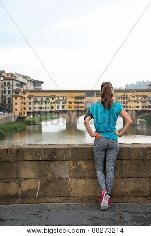 Fitness Woman Looking On Ponte Vecchio In Florence, Italy. Rear View