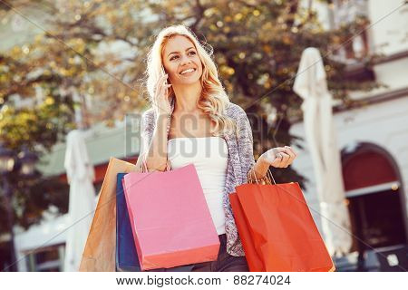 Young Blond Woman With Shopping Bags Using Mobile Phone