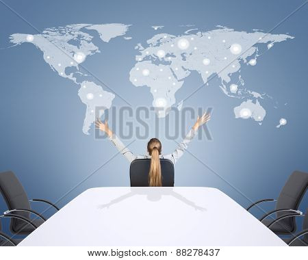 Rear view of businesswoman with hands up looking at world map