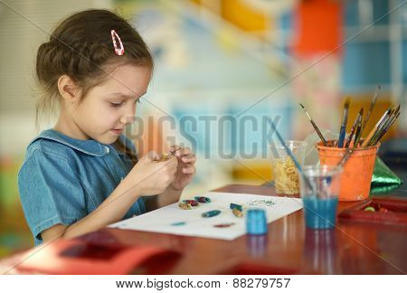 Little girl drawing with paints