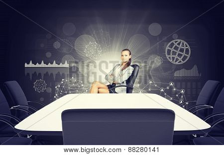 Business lady sitting at table with crossed legs and arms