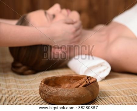 Beautiful young woman getting relaxing head massage. Focus on cinnamon