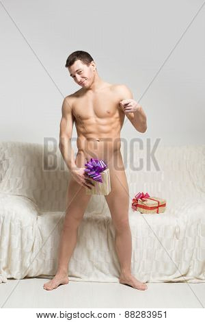 naked man on a couch with a gift