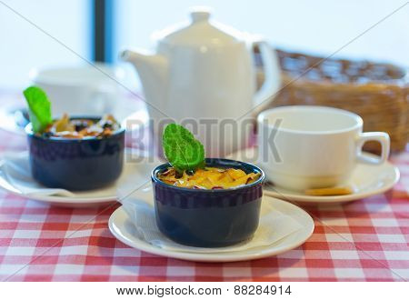 Fruit Pudding With Mint And Tea On A Checkered Tablecloth