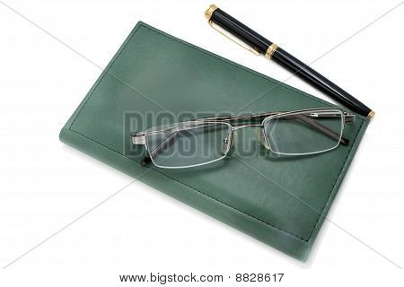 green notebook, spectacles and pen