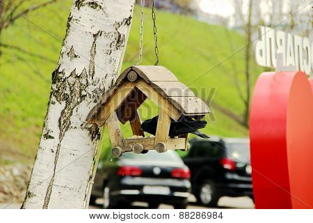 Pigeon feeding in decorative birdhouse with food.