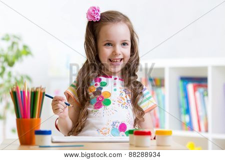 child girl paints in her nursery