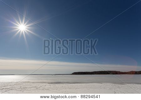 The spring sun in the afternoon over the lake covered with ice