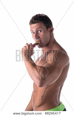 Shirtless muscular young man eating cereal bar