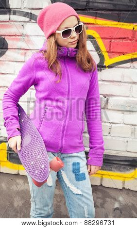 Blond Teenage Girl Holds Skateboard Near By Urban Wall