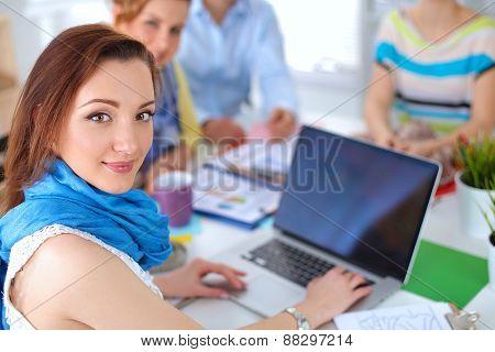 Portrait of attractive female  designer sittin on thesk  in office