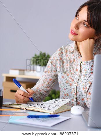 Young woman writes to diary on a white table